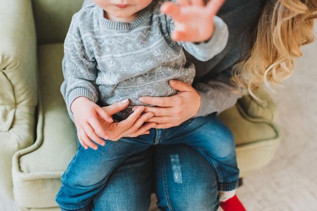Красивая молодая мать, держа ее милый сын на руках