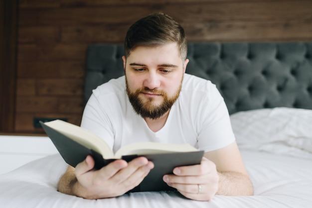 Закройте вверх по молодому красивому кавказскому человеку читая книгу в кровати