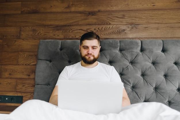 自宅からベッドで彼のラップトップに取り組んでいる若い白人男