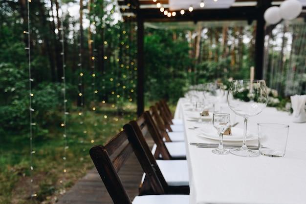 テントやパビリオンでの屋外での美しい結婚式のためにセットアップされたゲスト用の長いテーブル