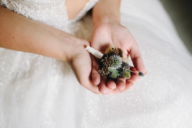 彼女の結婚式の日に繊細な花のブートニアを保持している白人の花嫁のクローズアップ