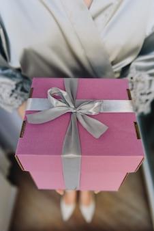 Крупным планом красивой подарочной коробке в руках молодой кавказской женщины