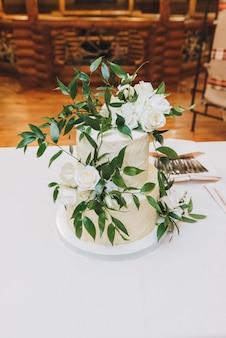 Красивый двухуровневый свадебный торт, украшенный листьями, вертикальное изображение