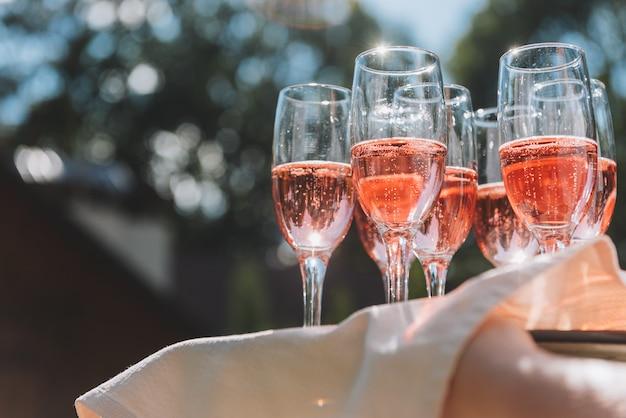 Поднос с бокалами летнего розового игристого вина для гостей на свадебном приеме в солнечных лучах