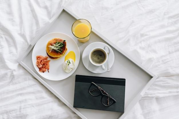 栄養価の高いおいしい朝食をグラスと本の上面とトレイ上のベッドでコーヒーを飲みながら