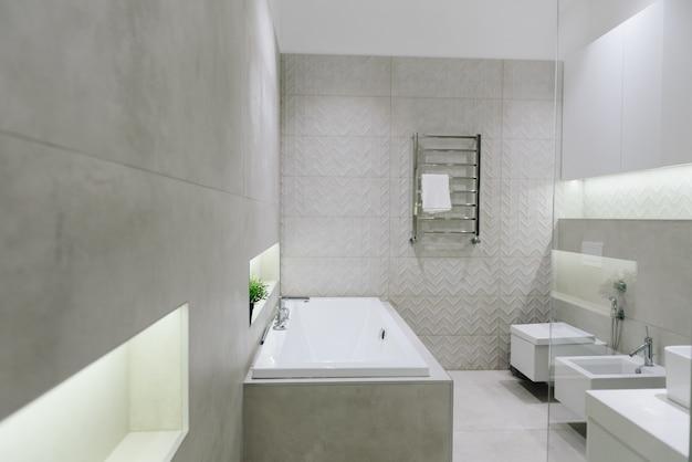 Стильный современный интерьер ванной комнаты, красивый минималистичный дизайн с туалетом, биде, ванной
