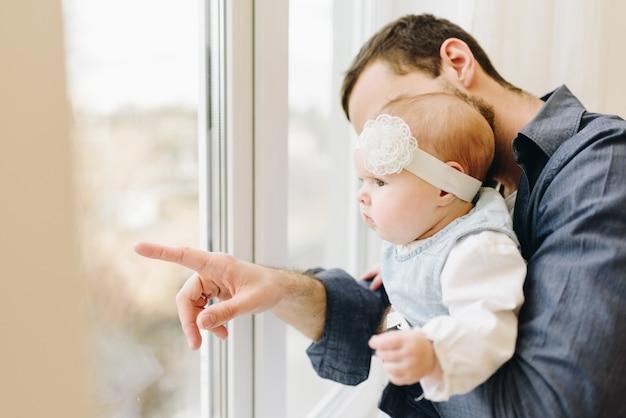 ウィンドウで何か彼の女の赤ちゃんを示す若い白人の父