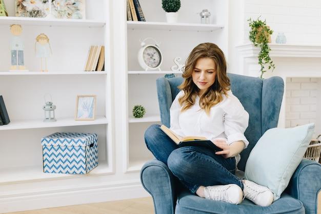 Умная молодая кавказская женщина читая книгу в комнате