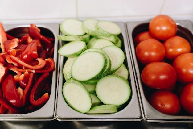 Разнообразные нарезанные овощи, приготовленные для приготовления на профессиональной кухне, такие как сладкий перец, цуккини, помидоры