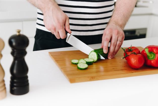 ナイフでモダンな白いキッチンで素敵な健康的な野菜の食事やサラダを調理する白人の男の手のクローズアップ