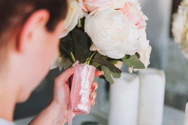 Профессиональный женский флорист работает над свадебным букетом невесты