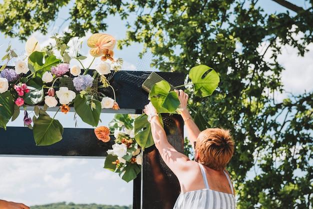 珍しい黒のウェディングアーチを飾る女性の花屋