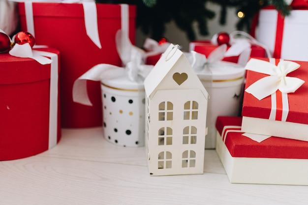 Новогодние подарки и предметы в красно-белых тонах под елкой