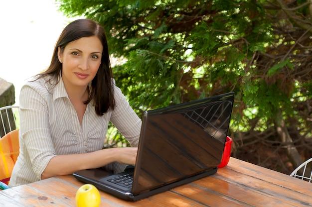 女性は、公園のラップトップを使用しています