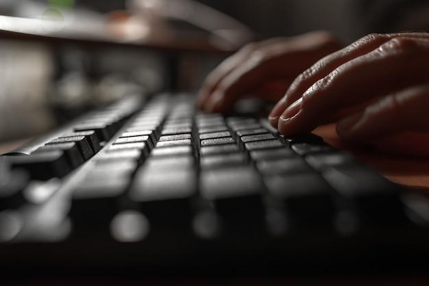 暗いところでコンピュータのキーボードを押す指。