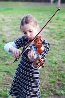 十代の少女がバイオリンを弾く