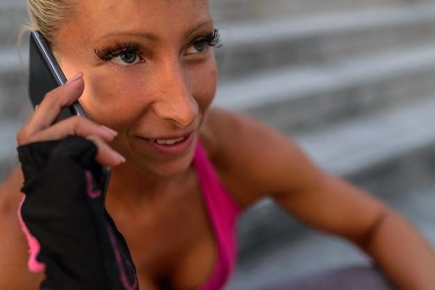 携帯電話を使用してスポーティな若い女性