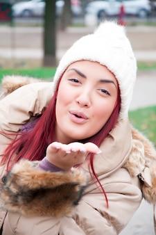 Прекрасная женщина с зимней одеждой отправляет воздушный поцелуй в камеру