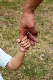 父の手は夏の森の自然の屋外で彼の子供の息子を導く、信頼家族の概念