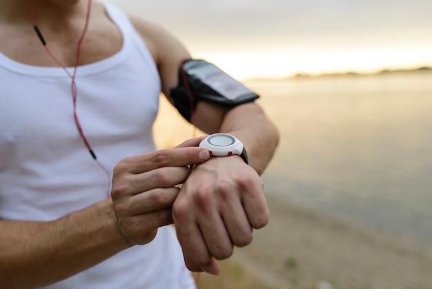 公園でスマートな腕時計を使用してフィットネス男