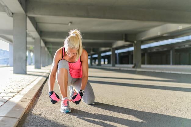 床に座ってランニングシューズの結び目のレースの女性の手。