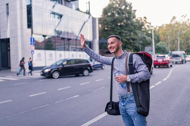 Молодой турист останавливает такси