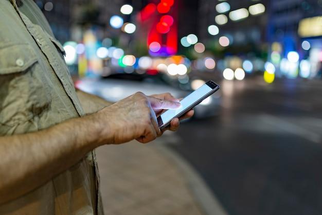 手で携帯電話が路上で男