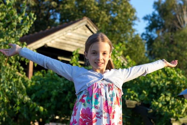 屋外に立っている間彼女の腕を大きく開いて幸せな十代の少女の正面図