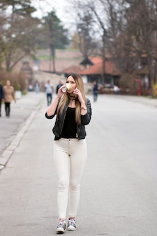 スマートフォンとコーヒーカップを持つ街の女の子