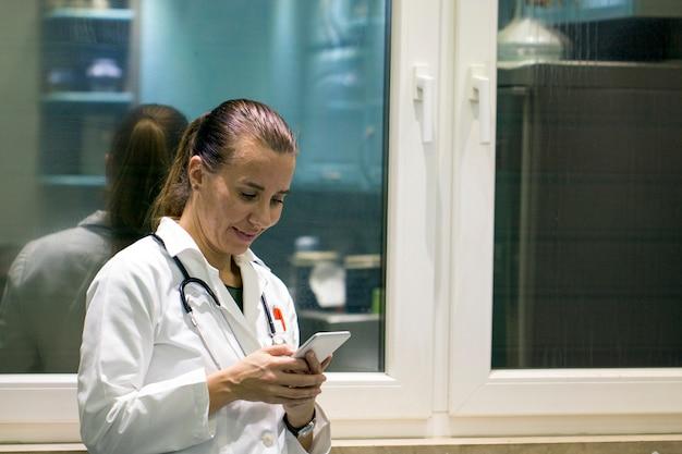 陽気な若い女性医師が立っているとスマートフォンを使用して