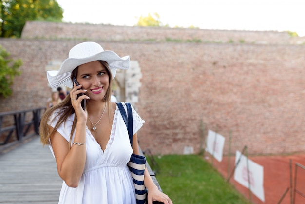 Счастливая молодая женщина разговаривает с телефоном на открытом воздухе