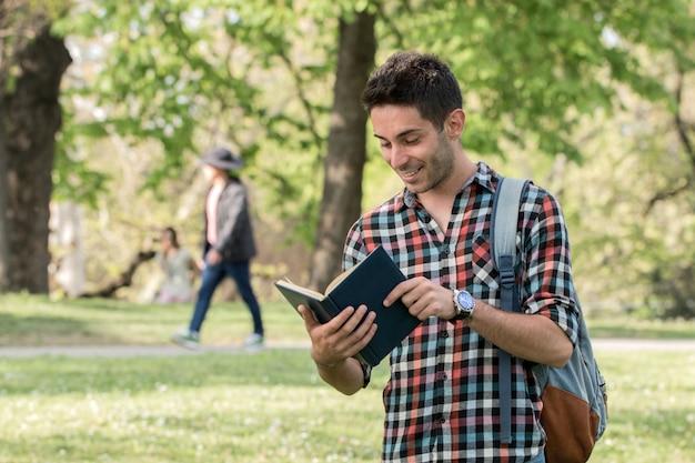 Парень студент делает домашнее задание в парке.