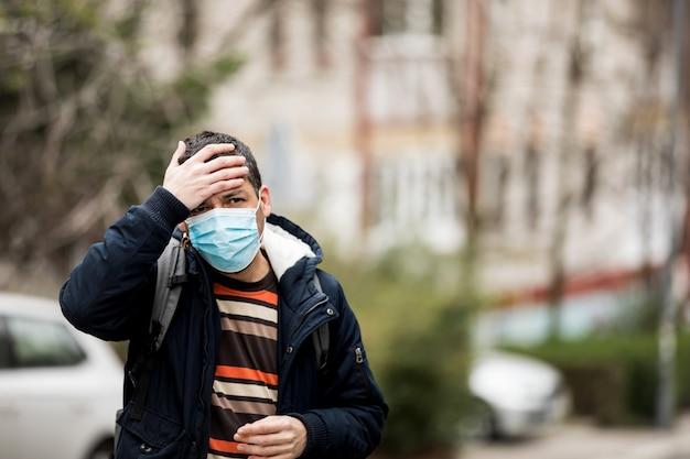 Зрелый человек носить маску и кашель, стоя в городе.