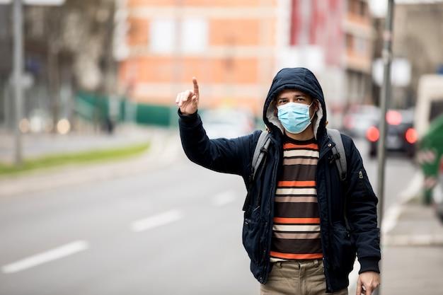 Коронавирус защита. зрелый человек в городе после рабочего дня, надев защитную маску на лицо.