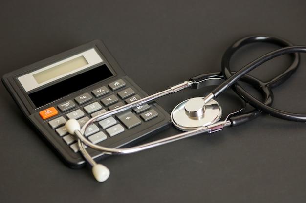 Стетоскоп на калькулятор, представляющий затраты на здравоохранение