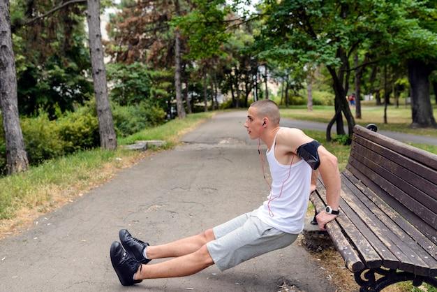 屋外の公園でプッシュアップをしているフィットネスマン