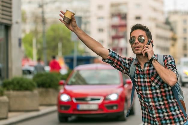 Человек приветствует такси на городской улице