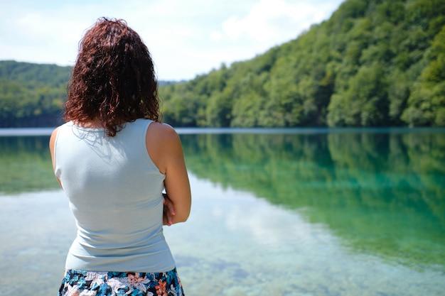 Молодая женщина смотрит на спокойное озеро в национальном парке плитвицкие, хорватия