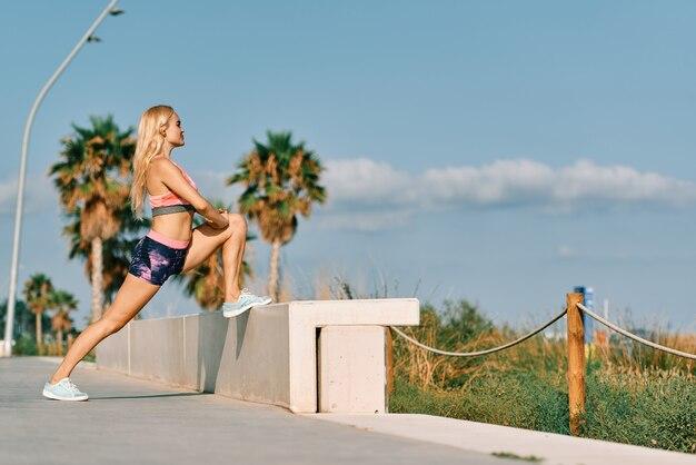 若い女性のウォーミングアップと夏の日の外ストレッチ