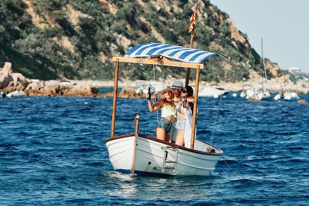 Группа молодых людей, веселиться в лодке - летняя концепция