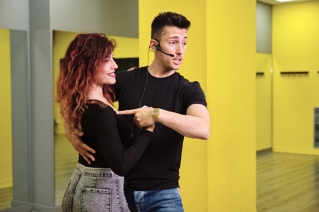 Молодая женщина и мужчина обучают сальсе и бачате