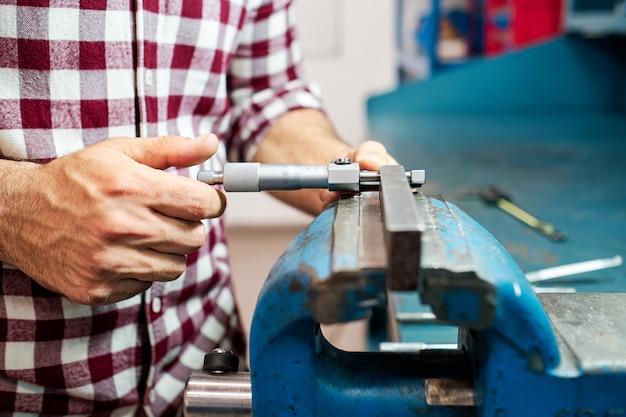 Рабочий измеряет микрометром в своей мастерской