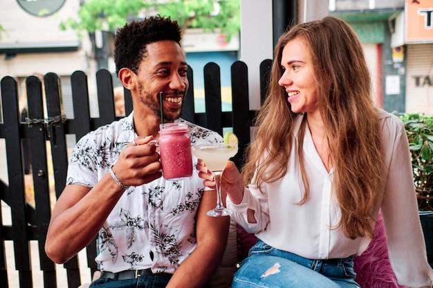 Молодые межрасовые пары в любви, попивая коктейль в баре летом