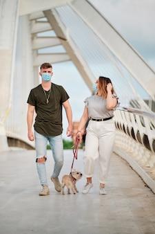 Пышная женщина и красивый мужчина в маске на прогулке с собакой - концепция коронавируса