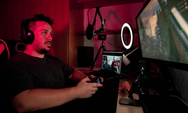 Геймер, играющий и транслирующий в прямом эфире с микрофонами и камерами