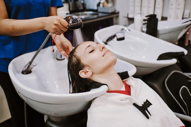 Счастливая молодая женщина с парикмахером, мытье головы в парикмахерской