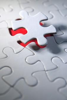 赤の背景に白の未完成のパズル、グループを完成