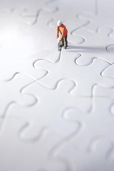 Миниатюрный человек строит головоломки, прокладывает путь для команды и работает концепции. концепция усилий