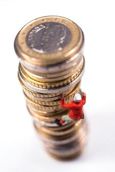 Миниатюрный альпинист залезает на стопку монет