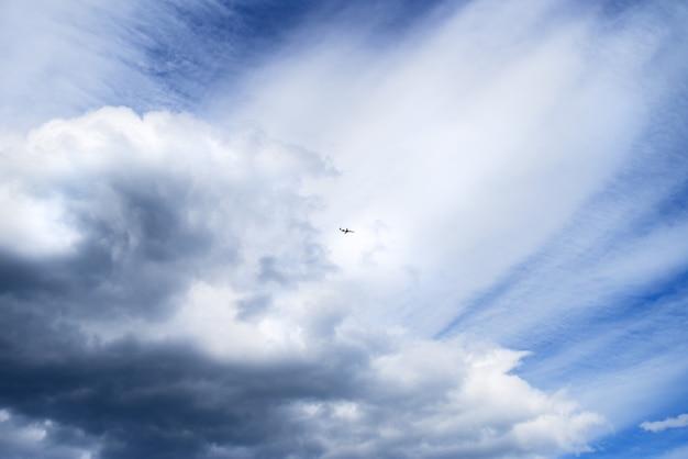 雲の間飛んでいる遠く離れた飛行機